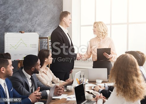 1070271598 istock photo Boss handshaking employee congratulating with promotion 1069974872