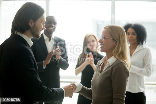 923041456 istock photo Boss handshaking employee congratulating with promotion while diverse colleagues applauding 923040758