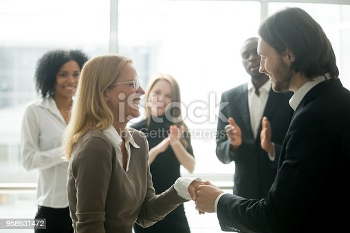 istock Boss handshaking rewarding female employee congratulating with promotion, colleagues applauding 958531472