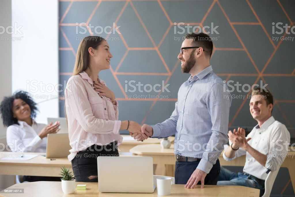 Boss handshaking successful female employee congratulating with promotion or rewarding stock photo