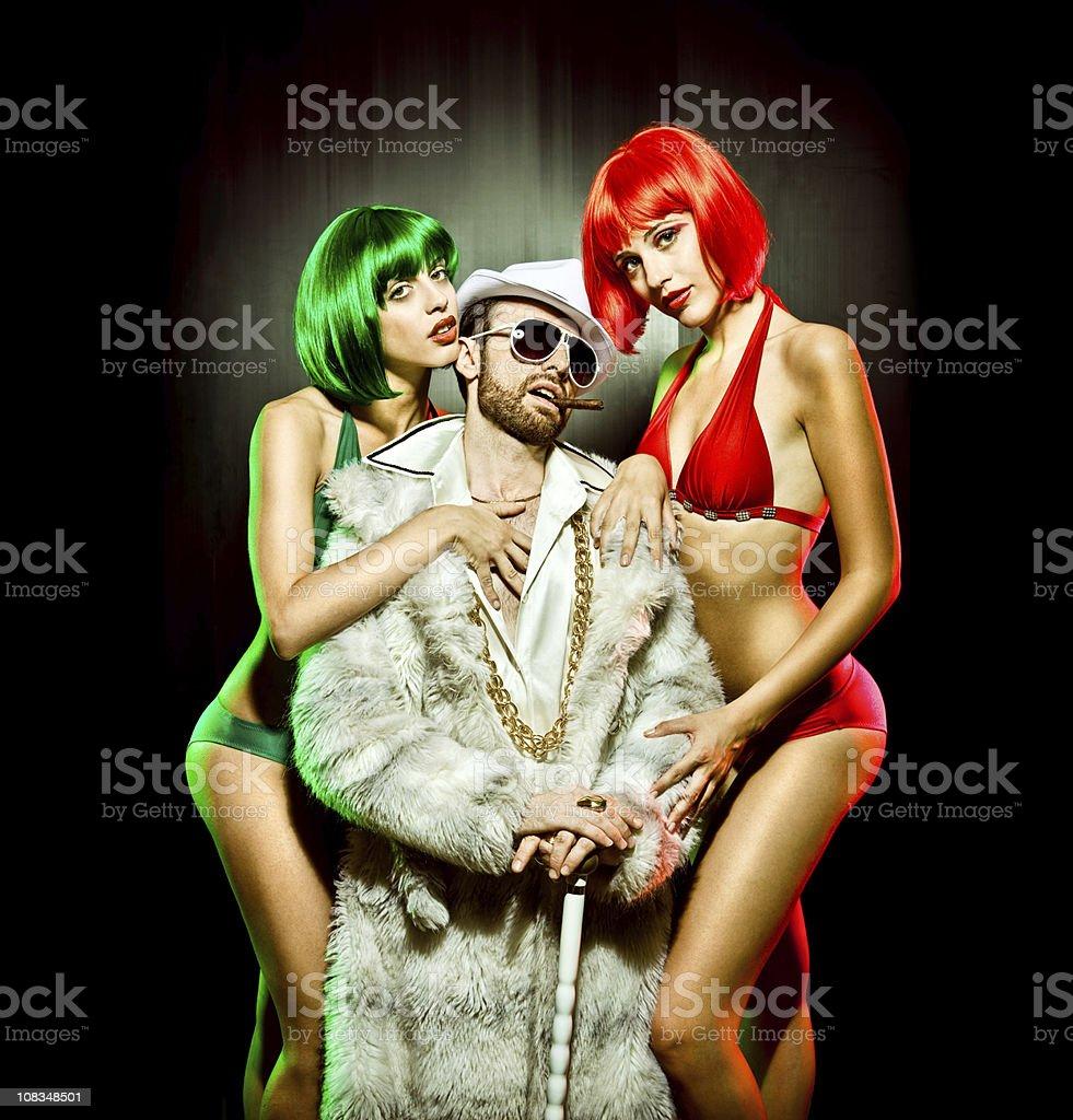 boss in fur with two girls red green bikini stock photo