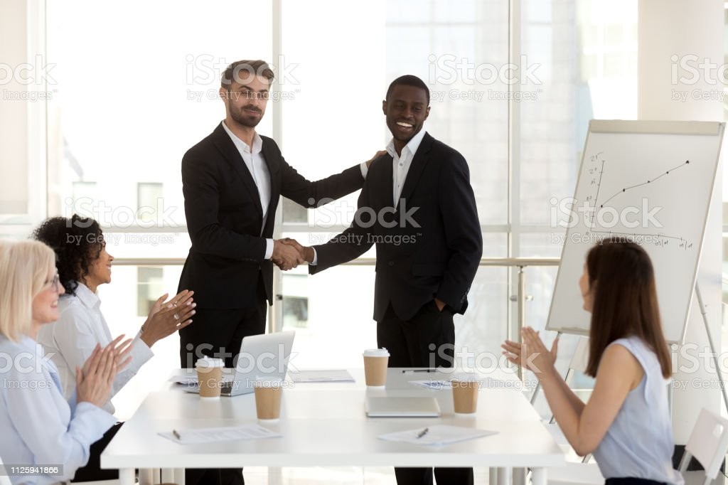 Diverse business people in boardroom, black man promoted rewarded for...