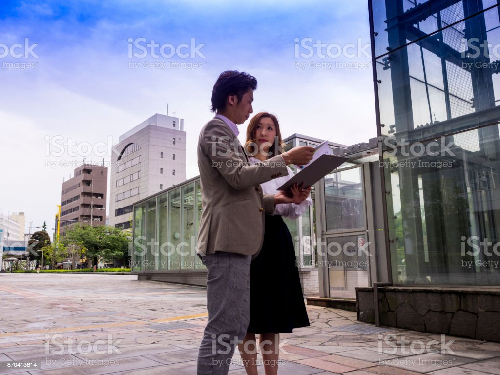 A boss is checking his assistant's business documents. stock photo