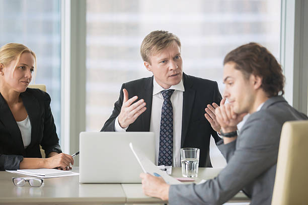 Boss nagging and dismissing intern stock photo