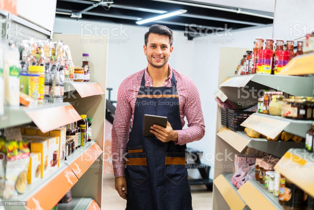 Boss of latin ethnicity dressed in a plaid shirt and an apron, in the...