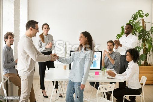 923041456 istock photo Boss promoting employee, hiring intern congratulating with handshake, team applauding 953656048