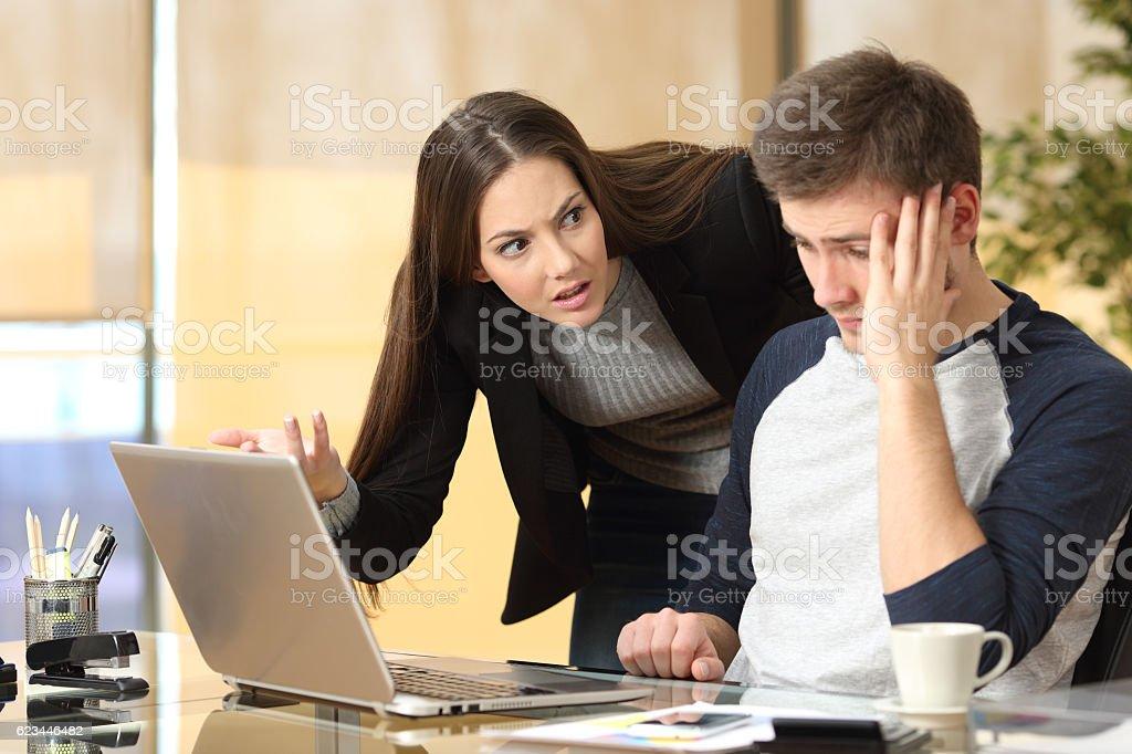 Boss scolding an employee Boss scolding a shameful employee at work in an office Working Stock Photo