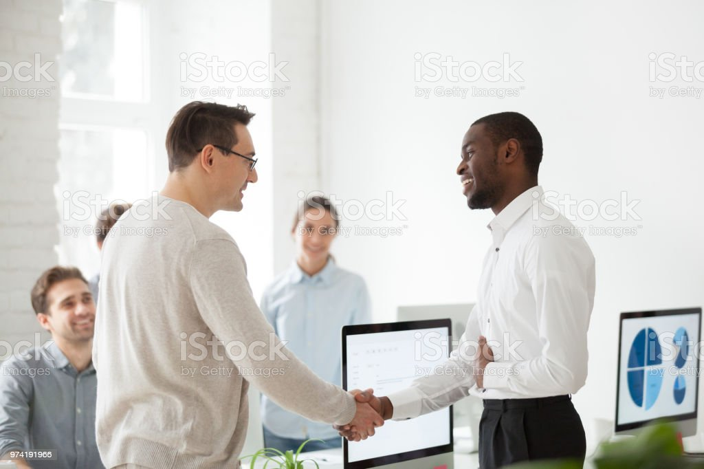 Middle aged boss shaking hand of proud employee congratulating with...
