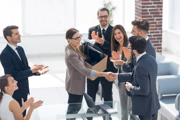 boss shaking hands with a new employee stock photo