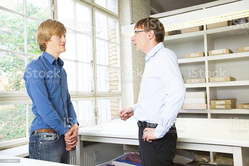 Boss talking to apprentice royalty-free stock photo