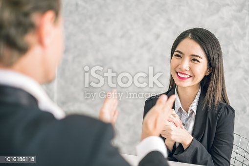 istock Boss/Business man employer admires young Asian business woman/staff/employee by thumb up and clap with smiling face for her success and good/best in work and recognition/appreciate. 1016186118