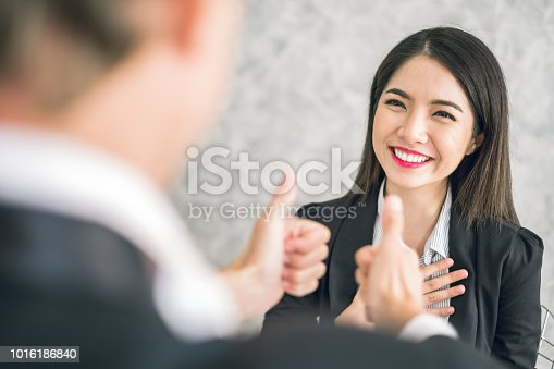 istock Boss/Business man employer admires young Asian business woman/staff/employee by thumb up and clap with smiling face for her success and good/best in work and recognition/appreciate. 1016186840