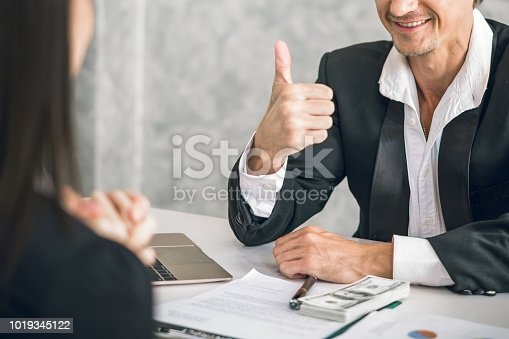 istock Boss/Business man employer admires young Asian business woman/staff/employee by thumb up and clap with smiling face for her success and good/best in work and recognition/appreciate. 1019345122