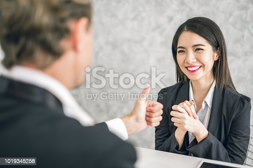 istock Boss/Business man employer admires young Asian business woman/staff/employee by thumb up and clap with smiling face for her success and good/best in work and recognition/appreciate. 1019345258