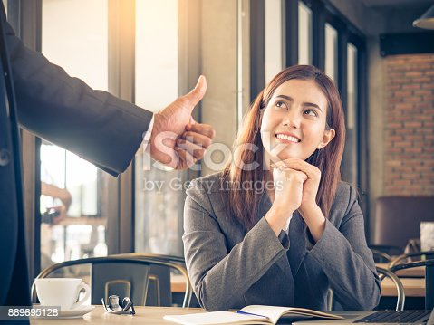istock Boss/employer admires to young Asian businesswoman/staff/employee with smiling face for her success and good/best in work. 869695128