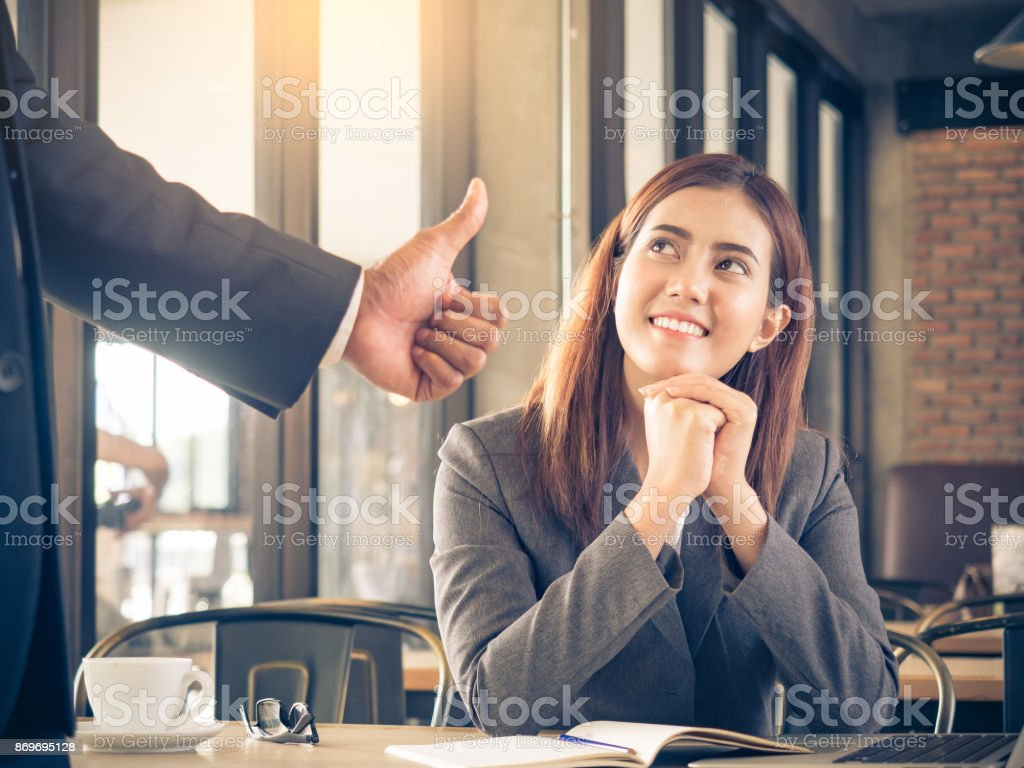 Boss/employer admires to young Asian businesswoman/staff/employee with smiling face for her success and good/best in work. stock photo