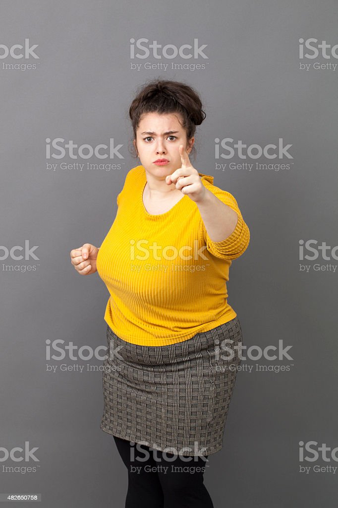 bossy 20s fat woman showing index and fist to denounce stock photo
