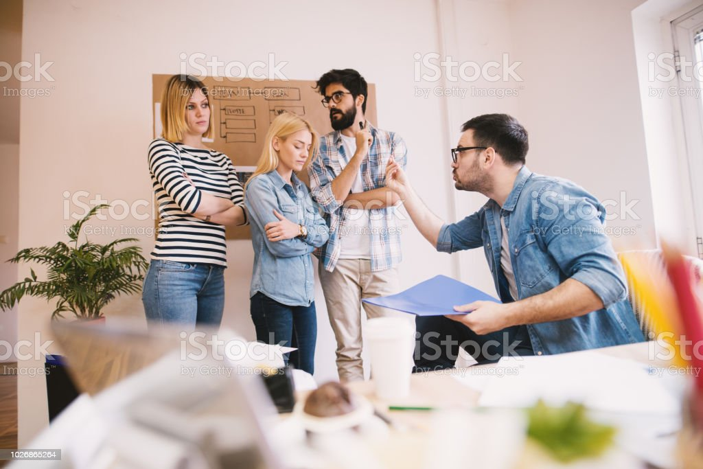 Bossy businessman is giving a lecture to his colleges because they did not accomplished their work. stock photo