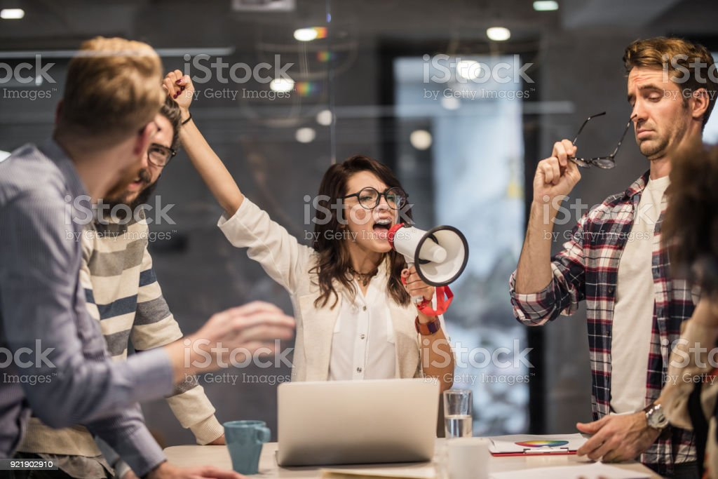 Bossy female leader encouraging her coworkers to work harder in the office. stock photo
