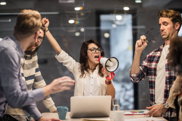 Bossy female leader encouraging her coworkers to work harder in the office. Young woman shouting through megaphone while having a meeting with her colleagues in the office. encouragement stock pictures, royalty-free photos & images