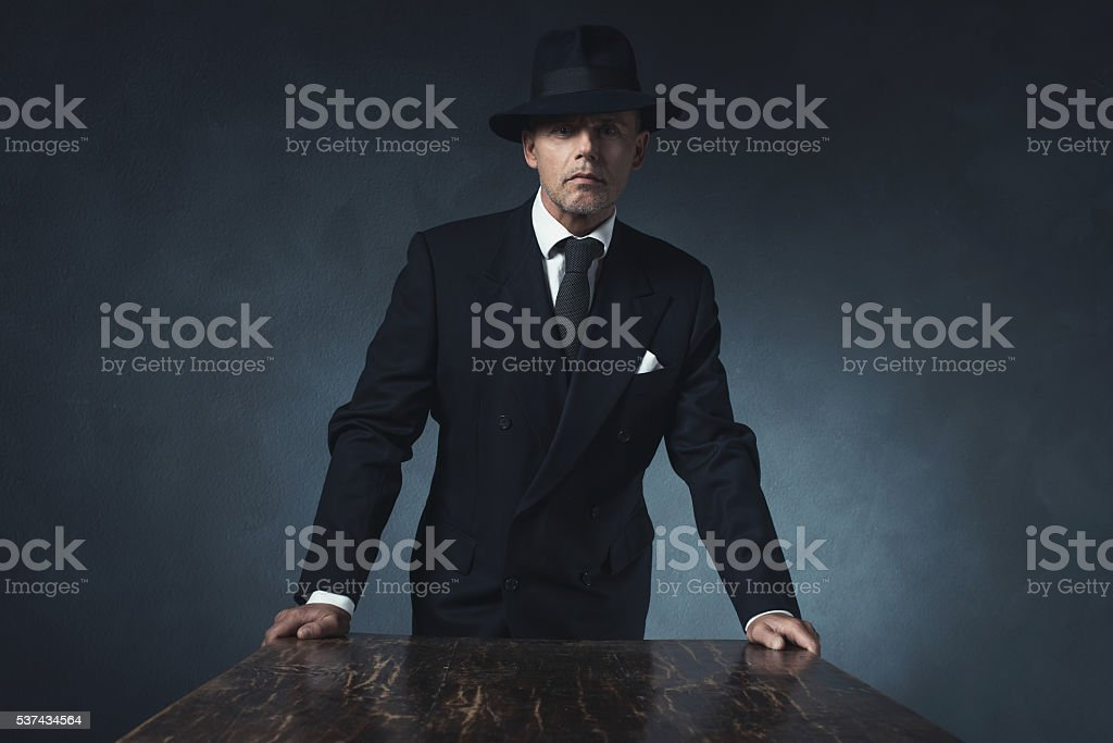 Bossy vintage 1940 businessman standing behind wooden table. stock photo