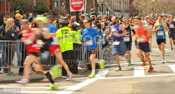 Boston, Mass., USA - April 15, 2013: Boston marathoners passing Boston Police officers on the corner of Hereford St. & Commonwealth Ave. just 2 blocks away and moments before the second of two bombs exploded on Boyleston St.