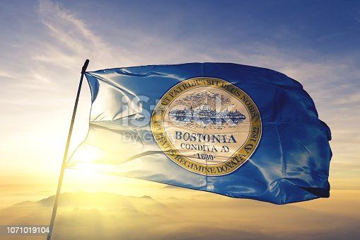 Boston city capital of Massachusetts of United States flag on flagpole textile cloth fabric waving on the top sunrise mist fog