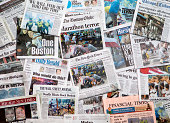 Carol Stream, IL, USA, April 20, 2013: A pile of local and national newspapers, including the Boston Globe, with headlines on the front pages reporting stories in the days immediately following the Boston Marathon Bombing