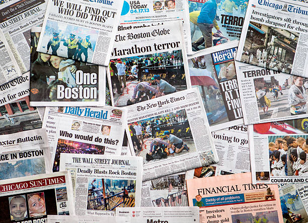 Boston Marathon Bombing headline collage featuring globe Carol Stream, IL, USA, April 20, 2013: A pile of local and national newspapers, including the Boston Globe, with headlines on the front pages reporting stories in the days immediately following the Boston Marathon Bombing medium group of objects stock pictures, royalty-free photos & images