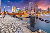 Boston, Massachusetts, USA harbor and cityscape at dusk.