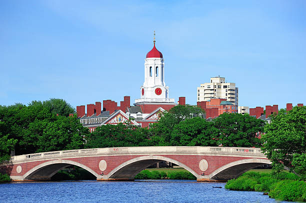 Boston John W. Weeks Bridge and clock tower over Charles River in Harvard University campus in Boston with trees and blue sky. harvard university stock pictures, royalty-free photos & images