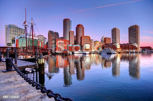 Downtown Boston Skyline along the Boston Harbor Waterfront. Photo taken along the harborwalk in the  South Boston southie neighborhood. The Boston cityscape is a mixture of old and new buildings. Boston is the capital and largest city in Masssachusetts. Boston is the largest city in New England