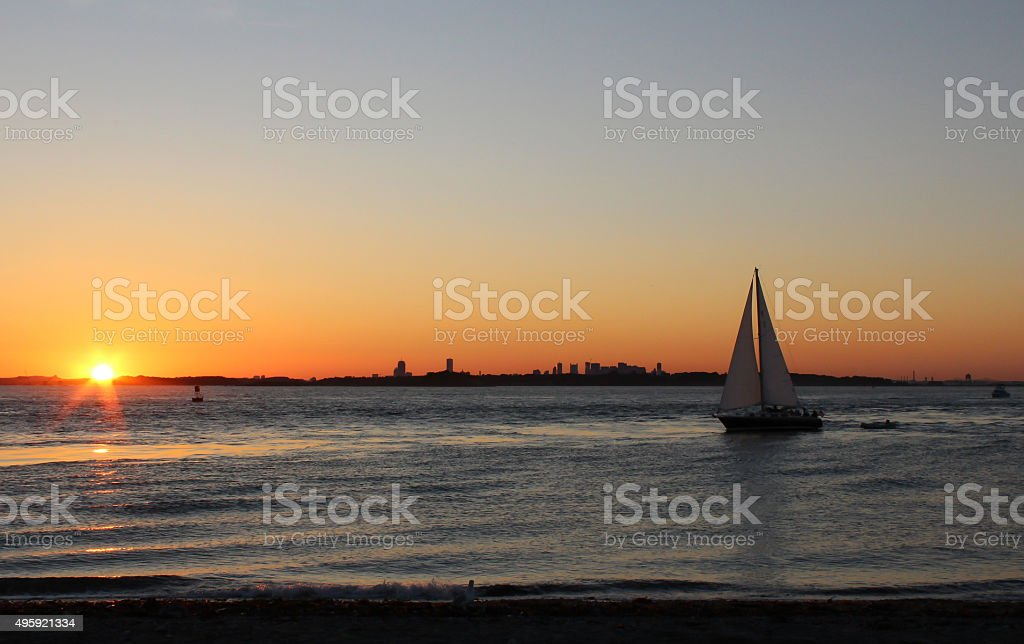 Boston Skyline with Sailboat at Sunset from Hull, Massachusetts stock photo