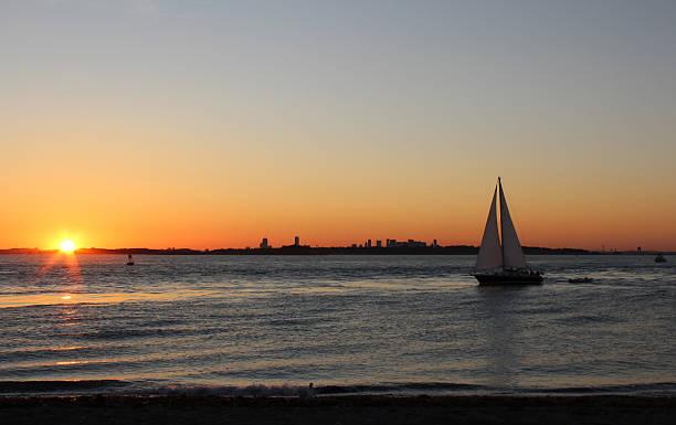 Boston Skyline with Sailboat at Sunset from Hull, Massachusetts stock photo