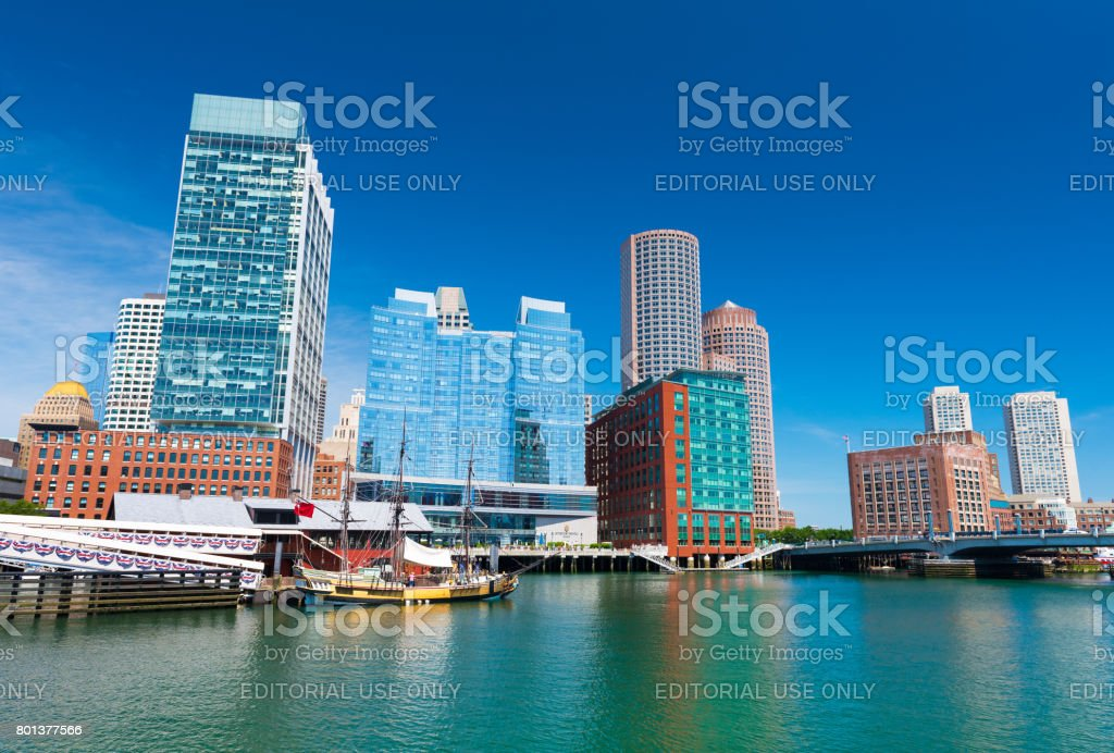 Boston, USA: Boston skyline, old historic ship in Tea Party museum and modern buildings in downtown reflected in the water of Boston harbor stock photo