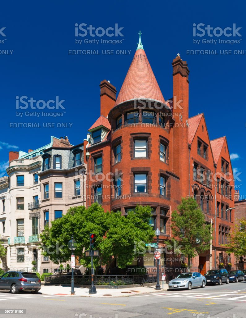 Boston, USA: Old historical building made of red brick and brownstone with cone rooftop in Boston back Bay district, against the backdrop of a clear blue sky stock photo