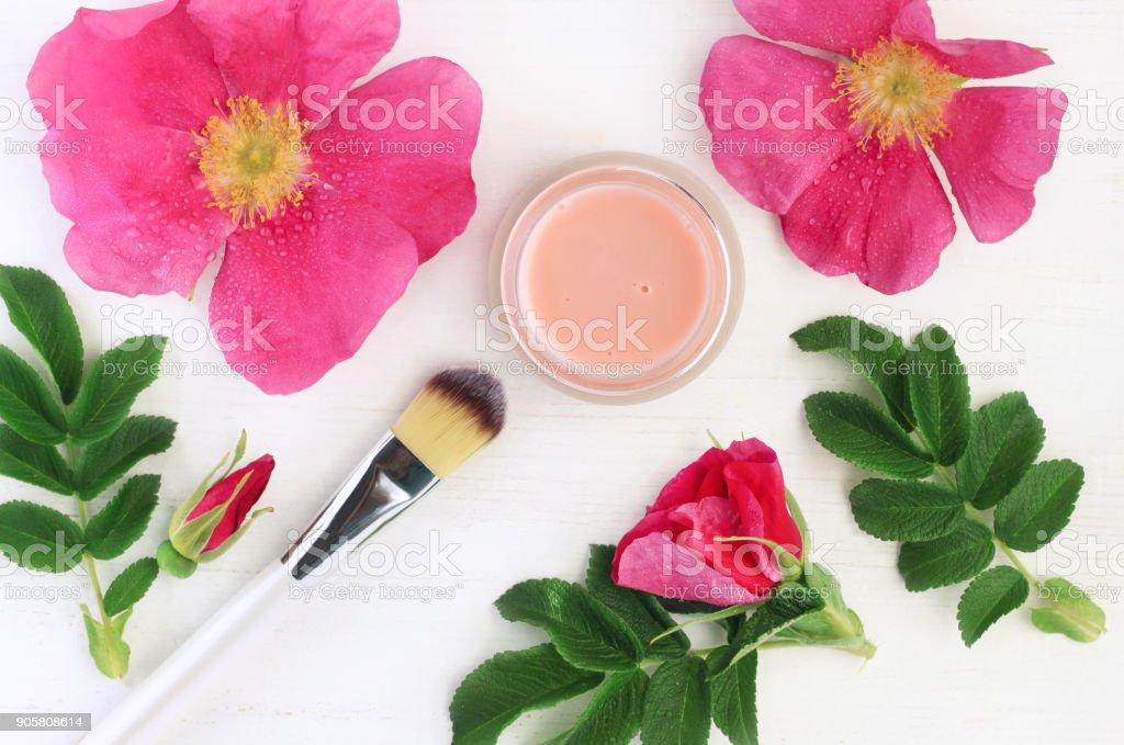 Botanical cosmetic product pink dogrose (Rosa Canina) composition. stock photo