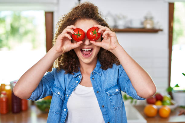 Both eyes covered with tomatoes stock photo