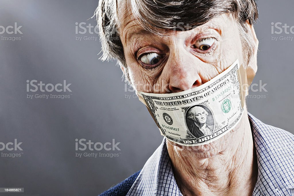 Bothered old woman looks down at dollar bill gagging her stock photo