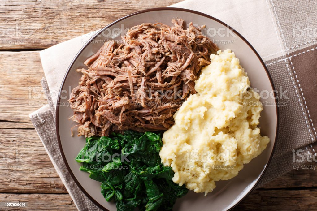 Botswana food - Seswaa stewed beef with Sadza from corn flour and spinach, close-up. horizontal top view stock photo
