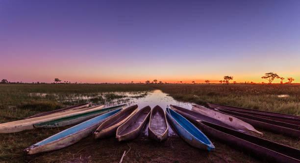Botswanian lokale mokoro Boote in der Sonnenuntergangszeit, am Ufer des Delta Okavango Fluss, Botswana – Foto