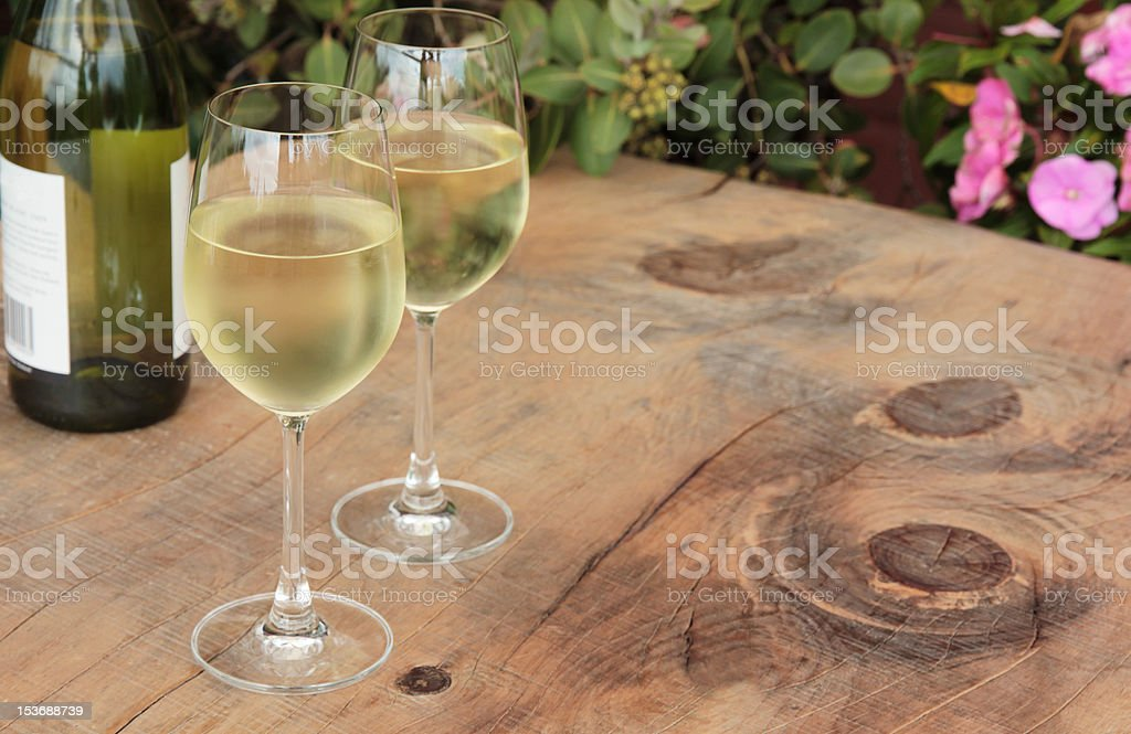 Bottle & Glasses of Wine on Outdoor Wooden Table stock photo