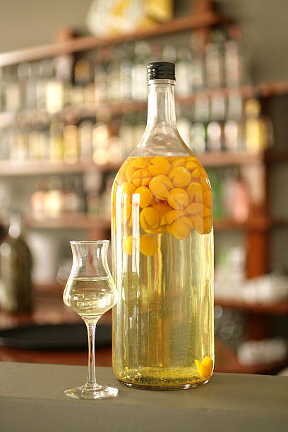 Bottle and cup of guaymanto fruit macerated in peruvian pisco Bottle and cup of aguaymanto fruit (physalis peruviana), also known as peruvian ground cherry, macerated in peruvian pisco, on a blurry bar background. pisco peru stock pictures, royalty-free photos & images