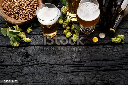 Beer and ingredients on black wooden table. Top View
