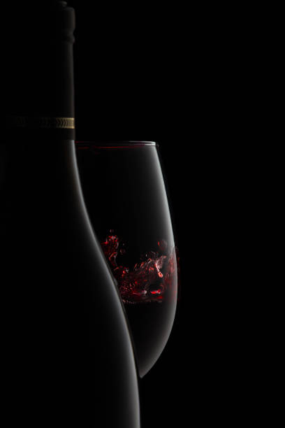 A bottle and glass of elegant red wine with splash. The silhouette of an unlabeled bottle and glass of elegant red wine with splash on the goblet, expressing luxury and stile, isolated on black. merlot grape stock pictures, royalty-free photos & images