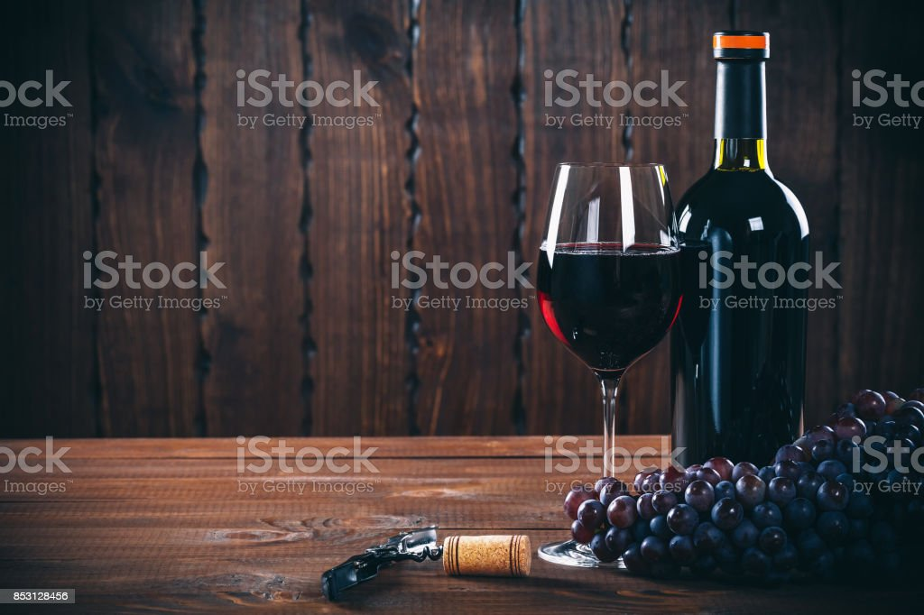 Bottle and glass of red wine, grape and cork on wooden background. stock photo