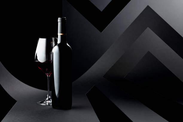 Bottle and glass of red wine on a dark background. stock photo
