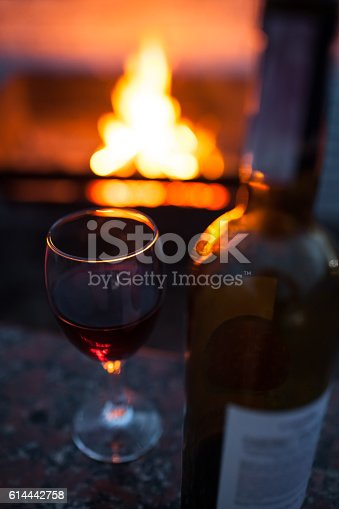 istock bottle and glass of red wine with fire on background; 614442758