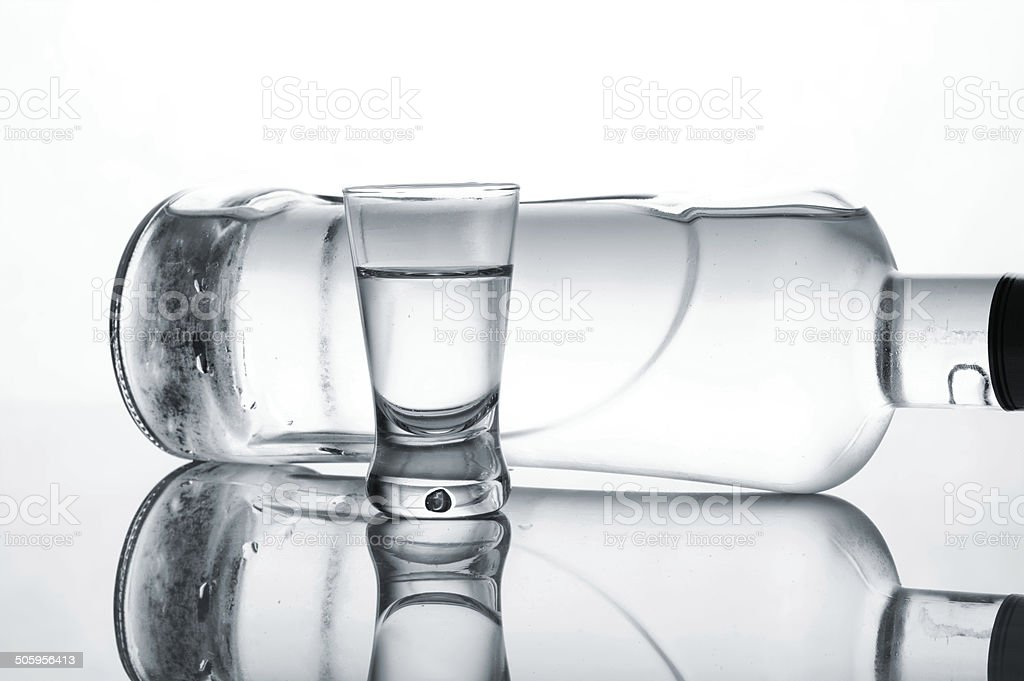 Bottle and glass of vodka lying isolated on white background stock photo