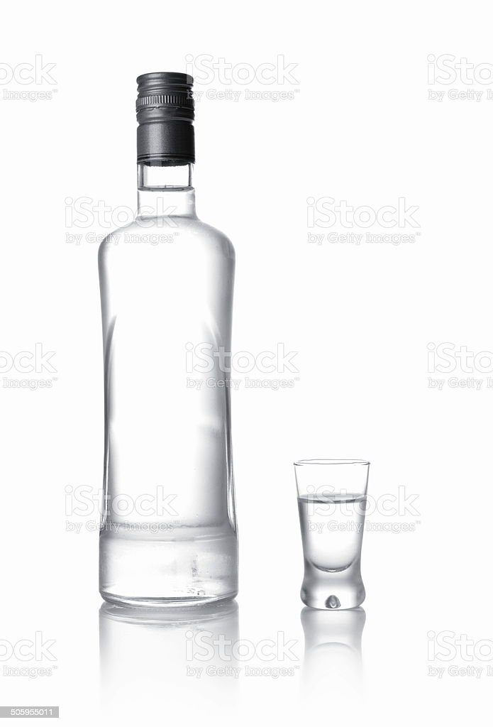 Bottle and glass of vodka standing isolated on white stock photo